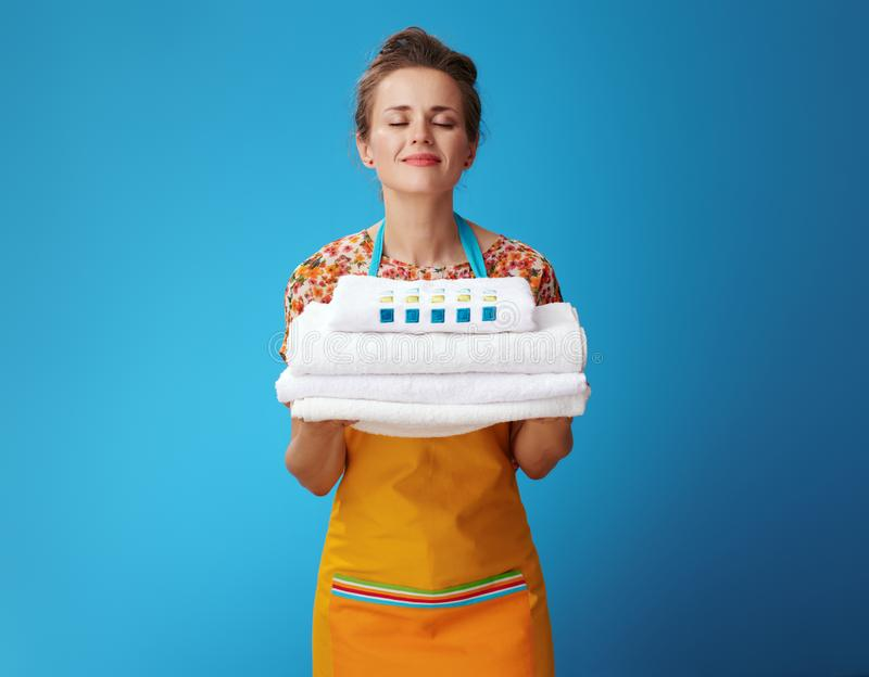 Happy young housewife enjoying fresh white linen on blue. Happy young housewife in orange apron enjoying fresh white linen on blue background. How to keep towels royalty free stock photography