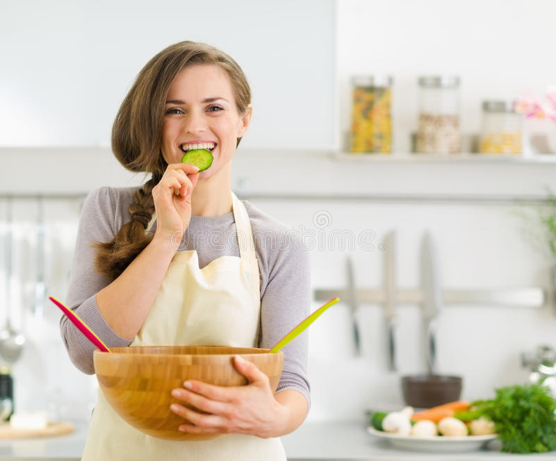 Happy young housewife tasting slice of cucumber stock images