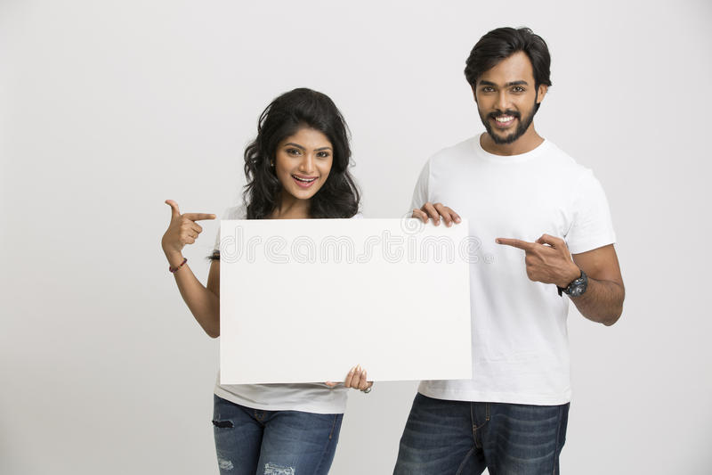 Happy young Indian people pointing a blank billboard royalty free stock image