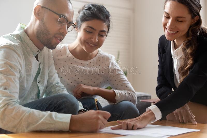Happy young indian woman watching african american husband signing contract. royalty free stock image