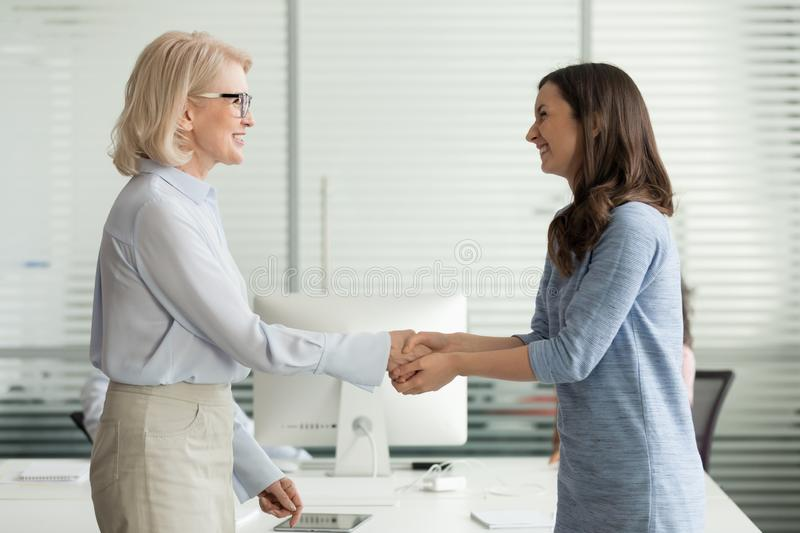 Happy young intern get hired rewarded handshaking female old boss stock photo