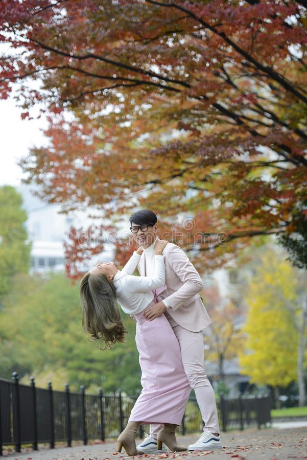 Happy young japanese couple under autumn trees stock photos