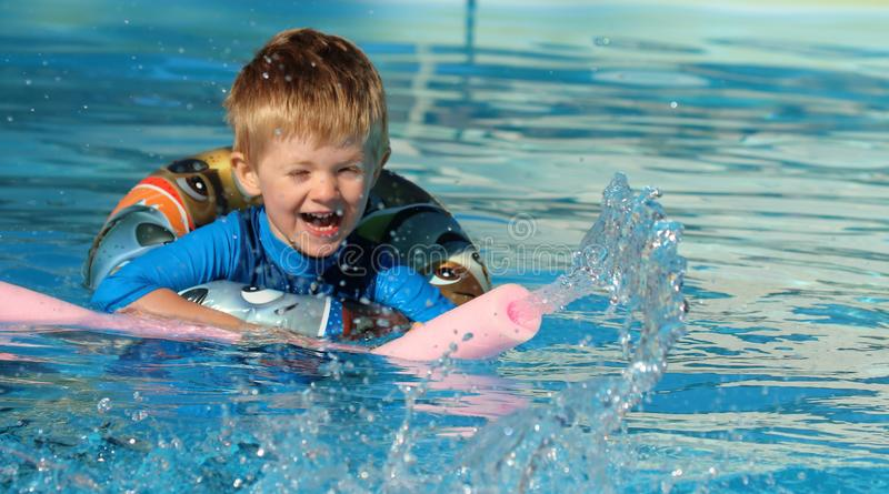 Young boy in the swimming pool with a rubber ring and a water spout. Happy young lad swimming in a pool with a rubber ring buoyancy aide and a water fountain royalty free stock photos
