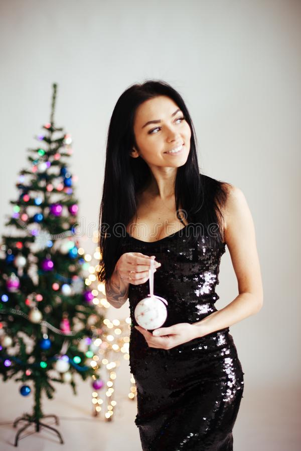 Happy young lady with gifts the Christmas. New year concept. Christmas tree, presents and gift boxes under it. New Year stock photos