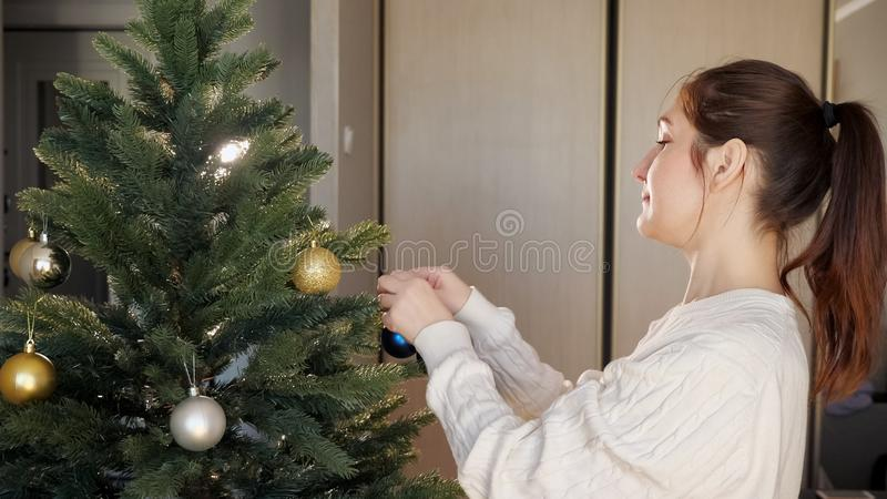 Happy young lady with ponytail decorates christmas tree royalty free stock photos