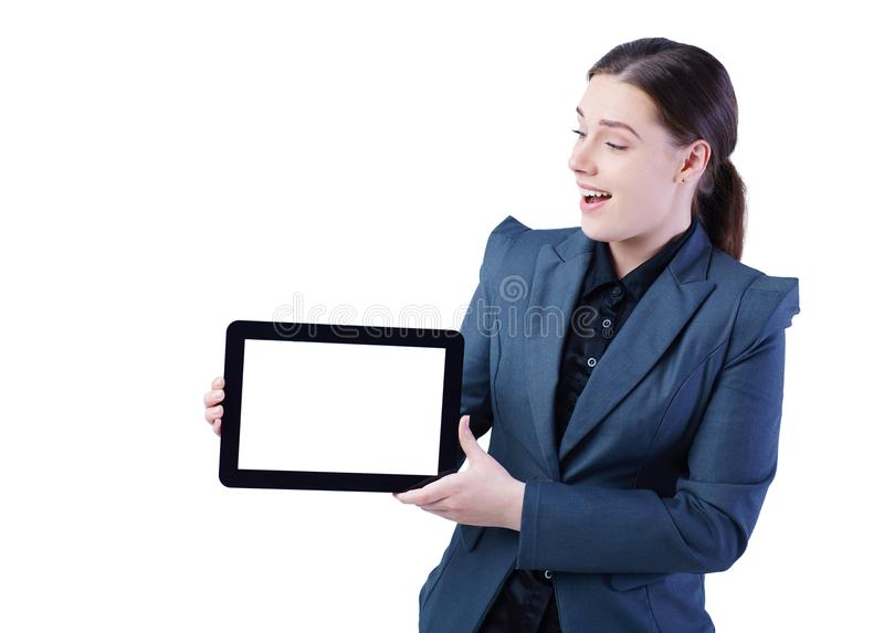 Happy young lady standing over white background showing display of tablet computer to camera. Focus on display. royalty free stock images