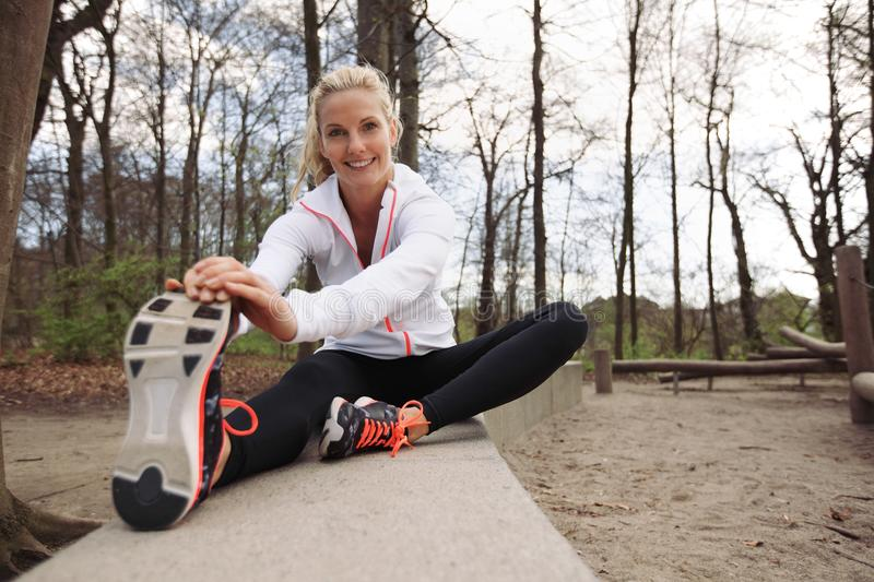 Happy young lady working out in nature. Happy and fit woman stretching her legs before training session in nature. Beautiful caucasian athlete exercising at the royalty free stock photography