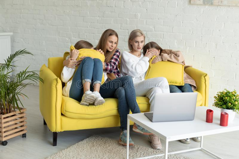 Happy young lesbian couple with daughters in casual clothes sitting together on yellow sofa at home, exited family royalty free stock image