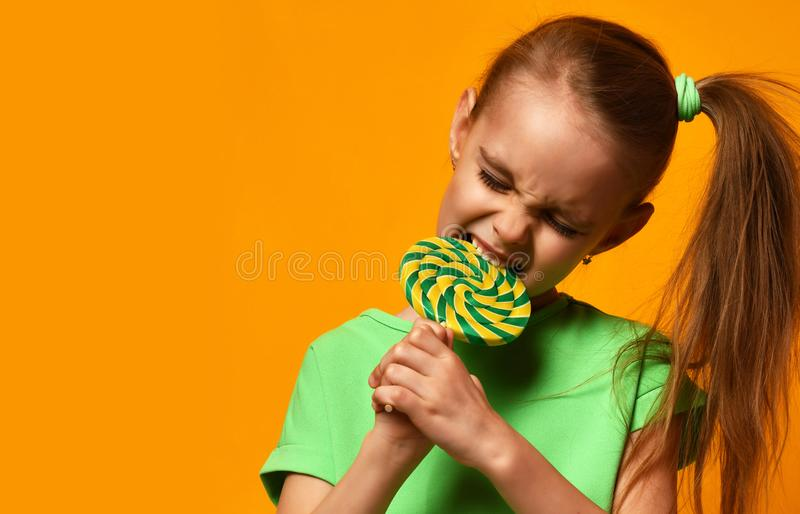 Happy young little child girl kid bite sweet lollypop candy stock photography