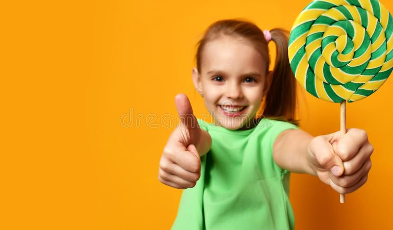 Happy young little child girl with sweet lollypop candy show thumbs up smiling with text copy space stock images