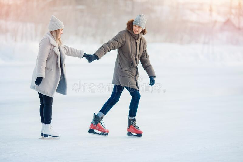 Happy young love couple hold hands, skate on rink, it snows in winter. Concept vacations outdoor activities royalty free stock images