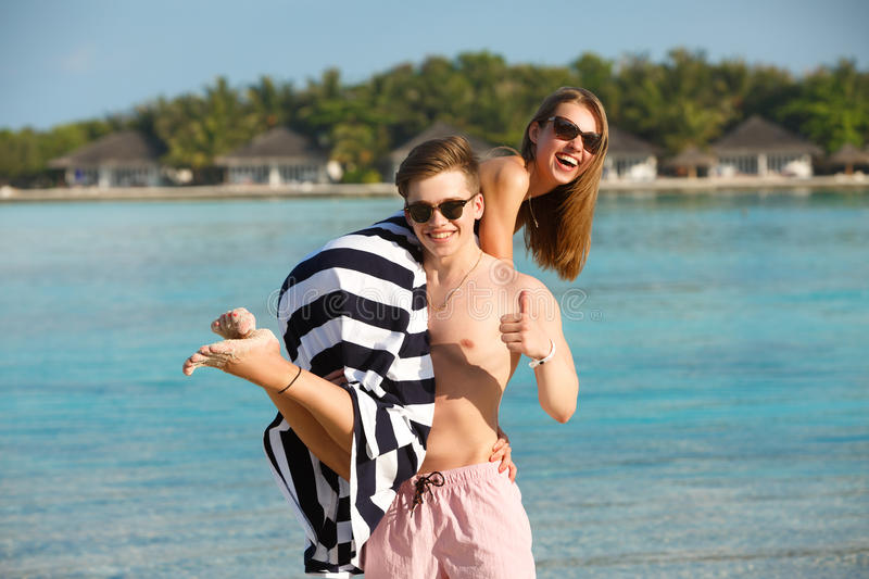 Happy young lovely couple have fun and relax on the beach. Man holds woman on his shoulder. Bungalows of spa resort royalty free stock photo