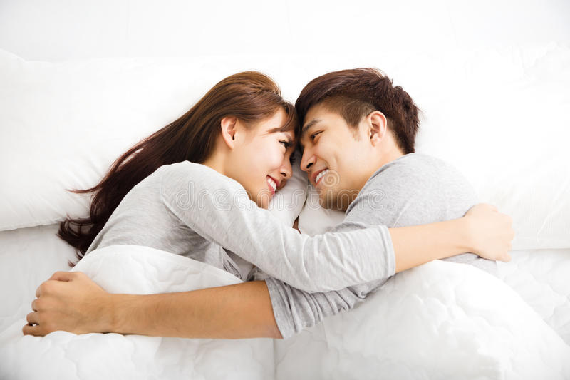 Happy young lovely couple lying in a bed. Happy young asian lovely couple lying in a bed stock image