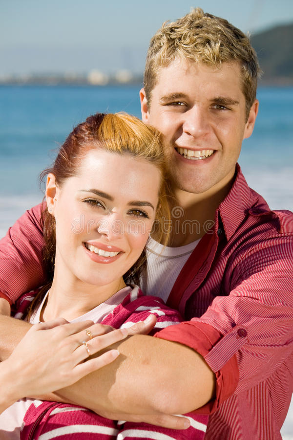 Happy young lovers. Smiling at the beach royalty free stock photo