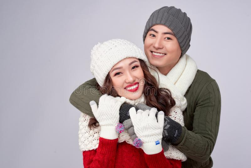 Happy young lovers in knitted woolen clothing hugging and looking together.  royalty free stock image