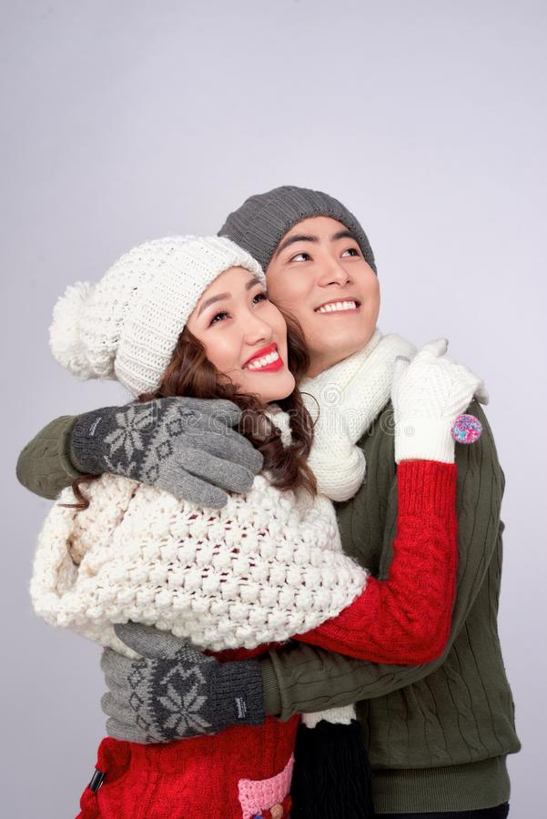 Happy young lovers in knitted woolen clothing hugging and looking together.  royalty free stock images