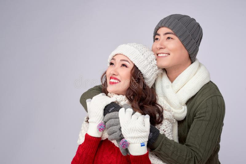 Happy young lovers in knitted woolen clothing hugging and looking together stock image