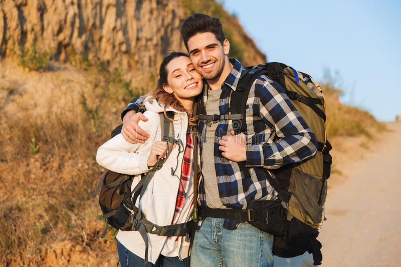Happy young loving couple outside with backpack in free alternative vacation camping. Photo of happy young loving couple outside with backpack in free royalty free stock photography