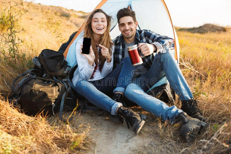 Happy young loving couple outside in free alternative vacation camping drinking hot tea. Photo of happy young loving couple outside in free alternative vacation stock image