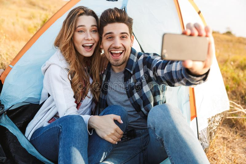 Happy young loving couple outside in free alternative vacation camping take a selfie by phone. Photo of happy young loving couple outside in free alternative royalty free stock image