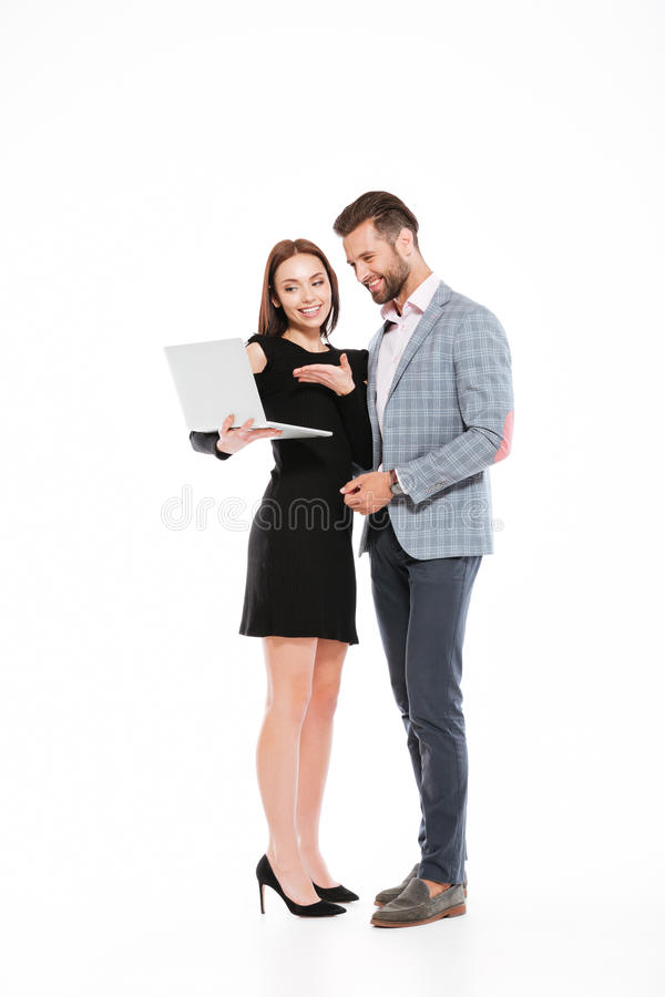 Happy young loving couple standing isolated using laptop computer. stock images