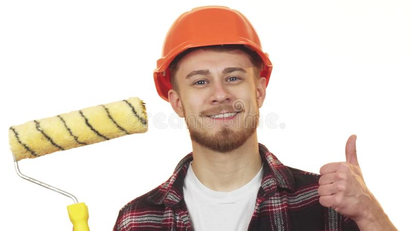 Happy young male builder holding paint roller showing thumbs up royalty free stock photos