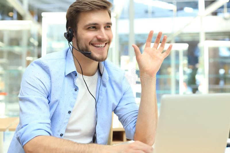 Happy young male customer support executive working in office stock photography