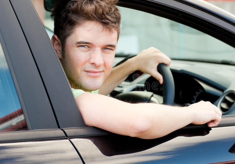Happy young male driver sitting in his car. And looking out of the window stock photos