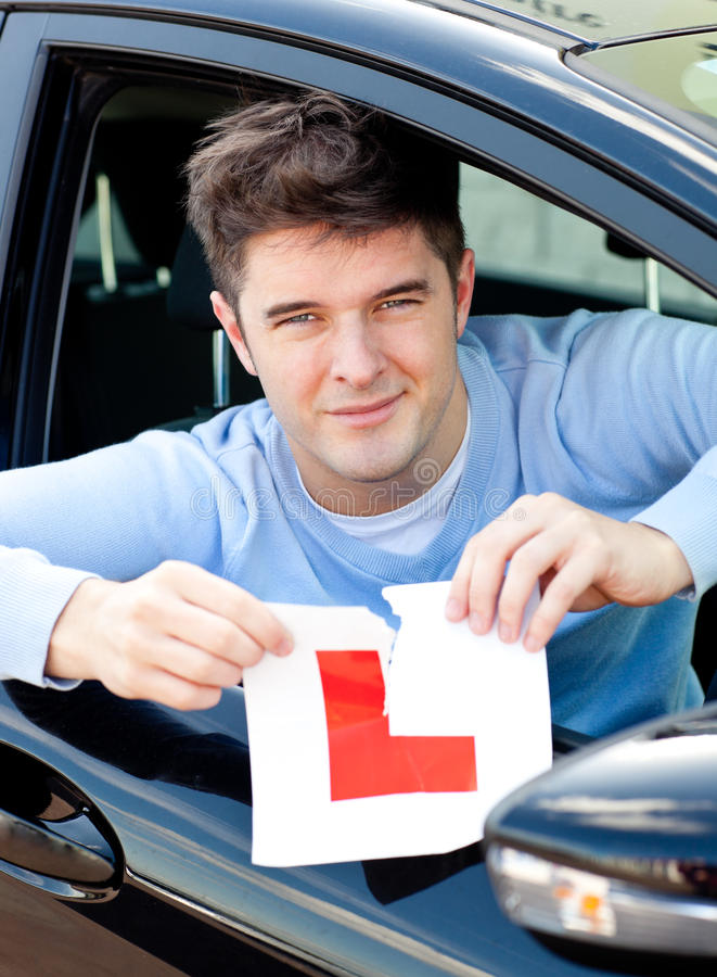 Happy young male driver tearing up his L sign. Sitting in his car royalty free stock photos