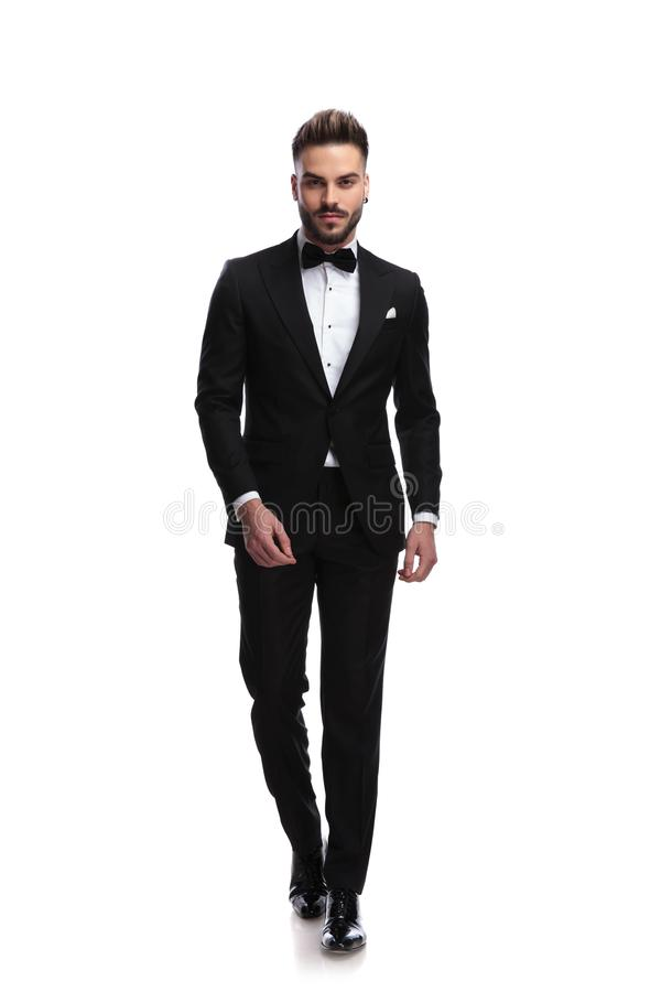 Happy young male fashion model in tuxedo is walking stock photography