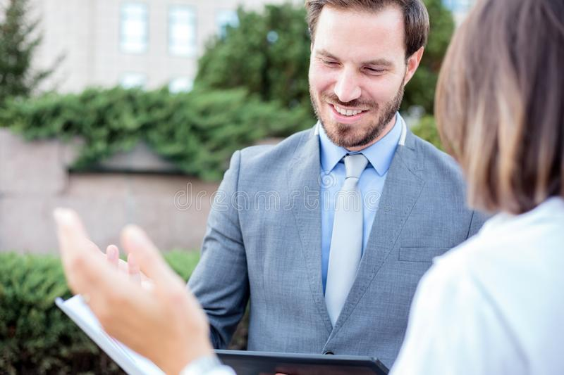 Successful young male and female business people meeting in front of an office building, talking and discussing. Happy young male and female business people stock image