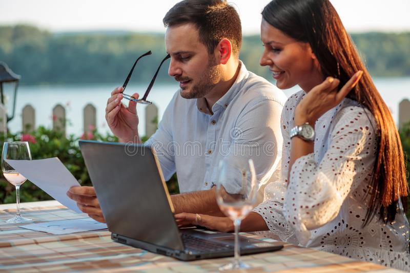 Happy young male and female business people meeting in a riverside restaurant, working on a laptop and looking at sale charts royalty free stock image