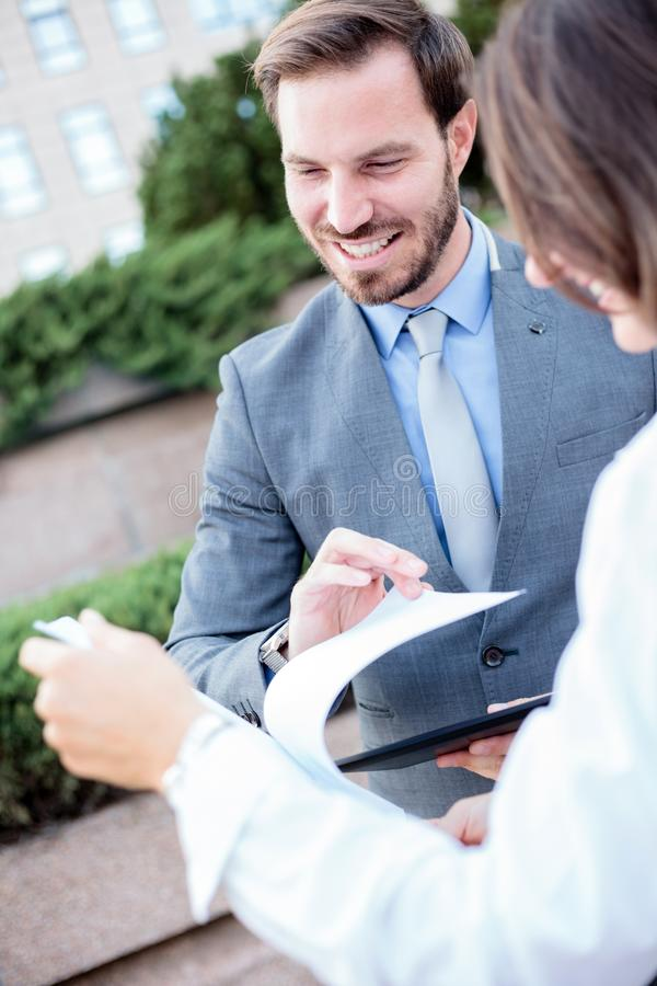 Happy young male and female business people talking in front of an office building, having a meeting and discussing stock photo