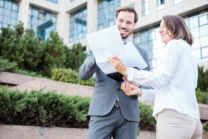 Happy young male and female business people talking in front of an office building, having a meeting and discussing. Looking at paper charts and reports. Low stock photos