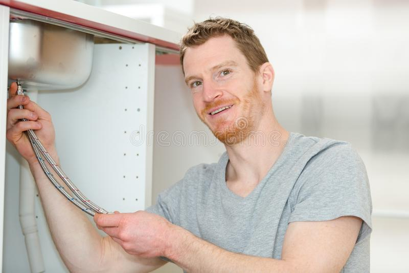 Happy young male plumber fixing faucet in kitchen royalty free stock photo