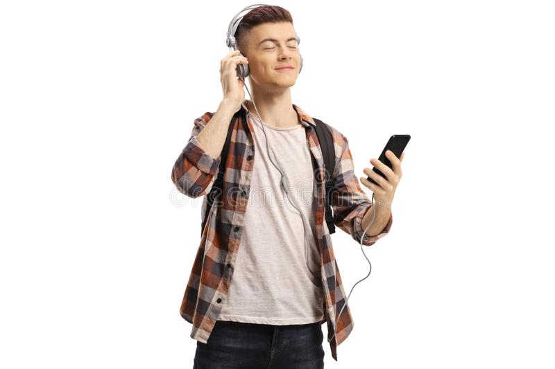 Happy young male student listening to music on headphones from mobile phone stock image