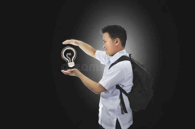 Happy young male student in school uniform with back pack beholding an idea. Light bulb idea concept. Success, creative, and idea stock photo
