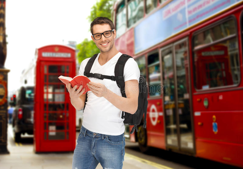 Happy young man with backpack and book travelling stock image