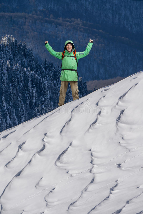 Happy young Man with backpack standing on snowy mountain slope. Alpinist or mountain hiker. Photo with place for text, copy space stock photo