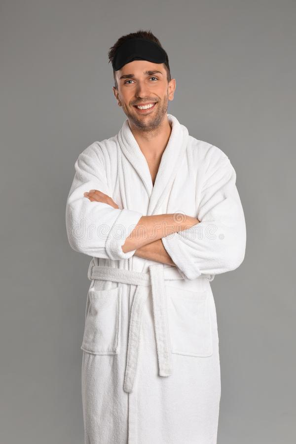 Happy young man in bathrobe on background stock photo