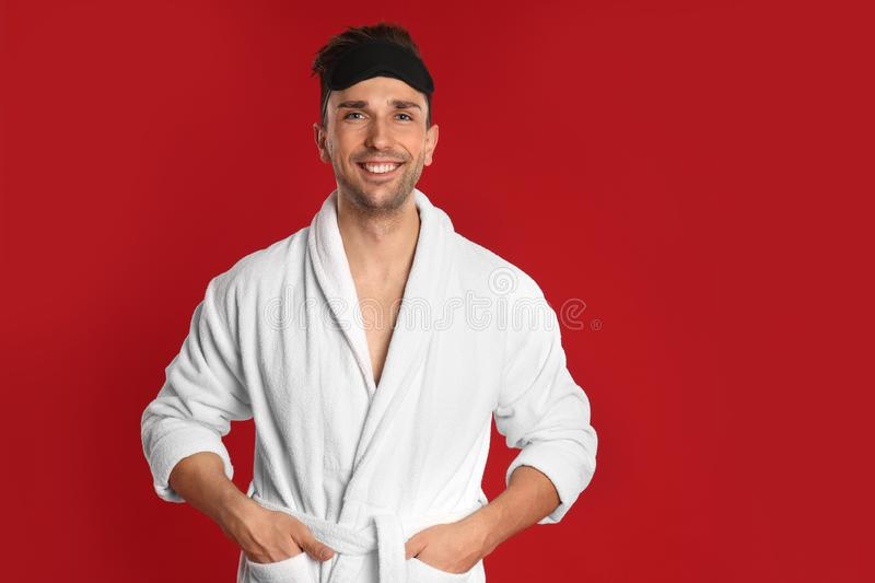 Happy young man in bathrobe on background royalty free stock image