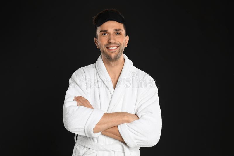 Happy young man in bathrobe and eye sleeping mask on background stock image