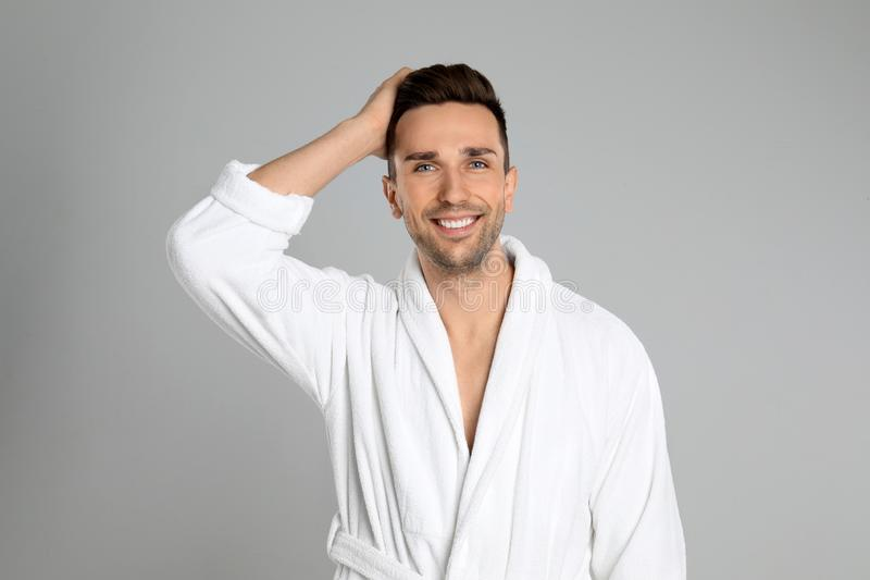 Happy young man in bathrobe on grey background stock photos