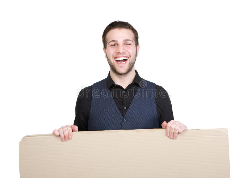 Happy young man with blank poster sign. Portrait of a happy young man holding blank poster sign on isolated white background royalty free stock photography