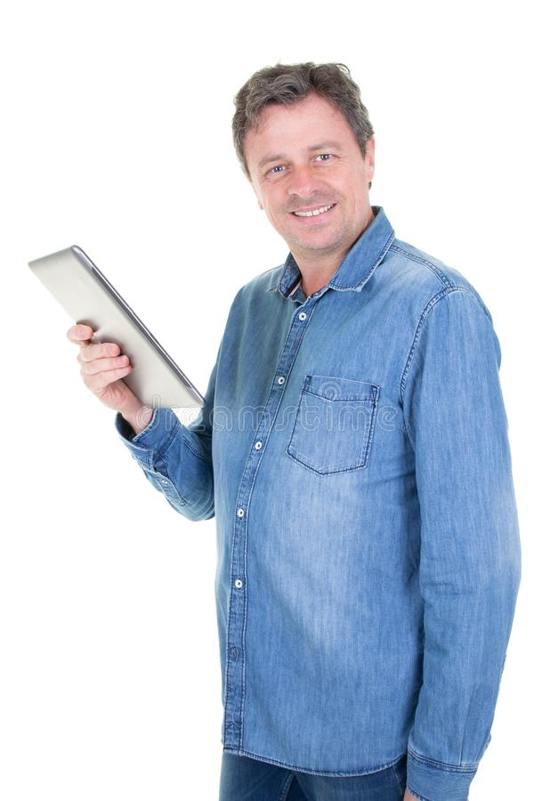 Happy young man in blue jeans shirt standing and using tablet over white royalty free stock photo