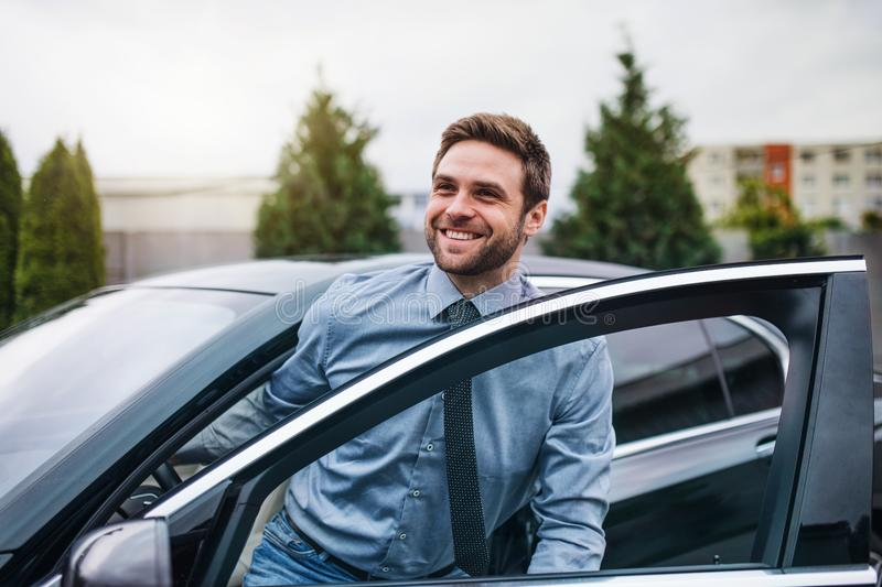 Young man with blue shirt and tie getting out of car in town. Happy young man with blue shirt and tie getting out of car in town royalty free stock image