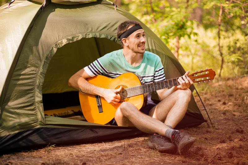 Happy young man camping and strum a guitar instrumental music to relax against background of forest sunset. Happy young man camping and strum a guitar royalty free stock photos
