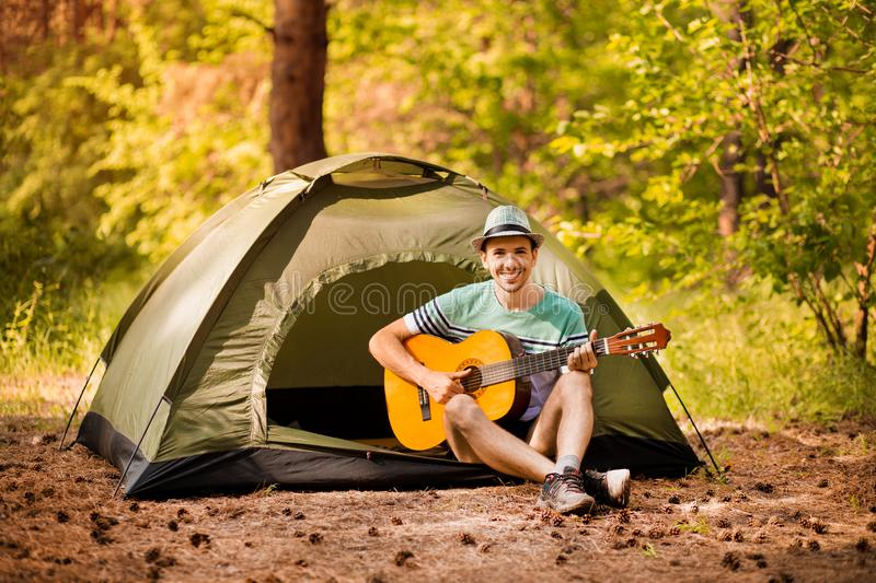 Happy young man camping and strum a guitar instrumental music to relax against background of forest sunset. Happy young man camping and strum a guitar royalty free stock photography
