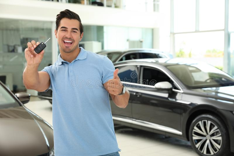 Happy young man with car key in modern auto dealership. Space for text royalty free stock images