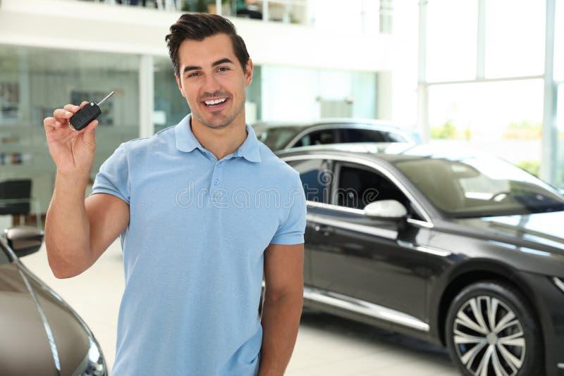 Happy young man  car key in modern auto dealership. Space for text. Happy young man with car key in modern auto dealership. Space for text stock images